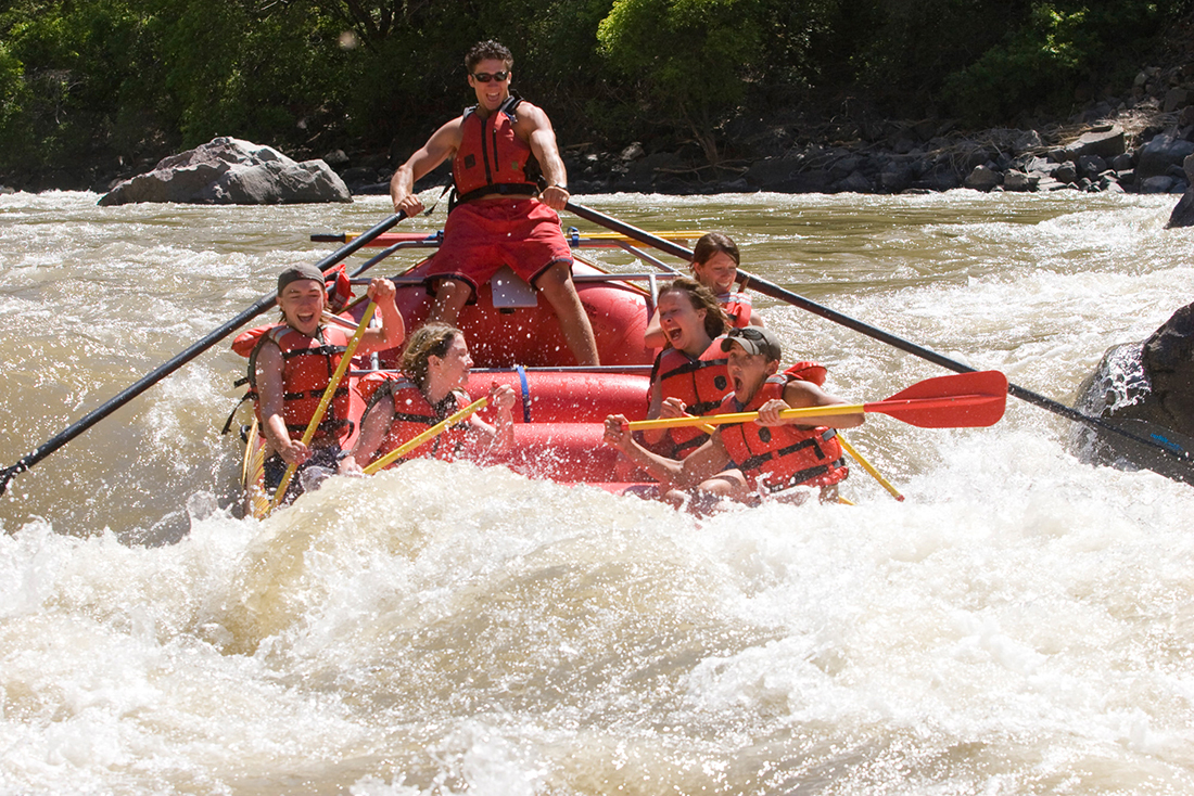 A red raft filled with paddles in rapids.