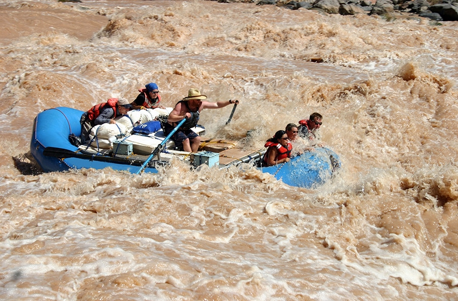 Rafters on a blue boat navigate their vessel through raging, muddy water.