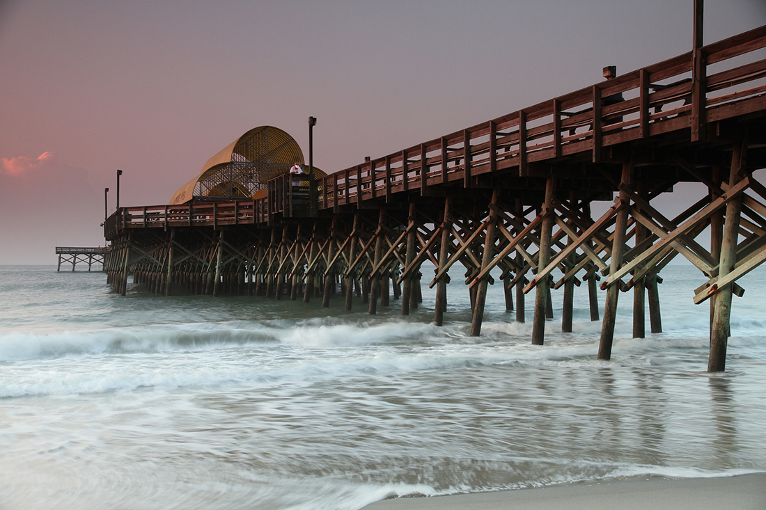 A pier on a beach at sunrise.