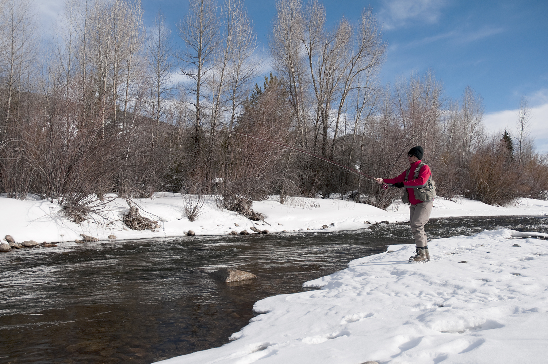 Fishing on a streem with snow-covered banks on each side.