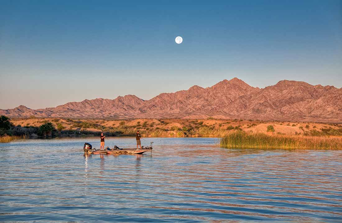 Two men in a boat fish on Lake Havasu under a full moon during the day.