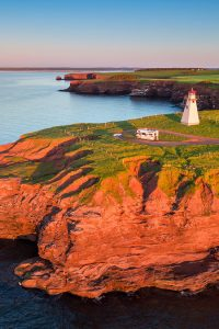 An RV drives near an elegant lighthouse on a bluff.