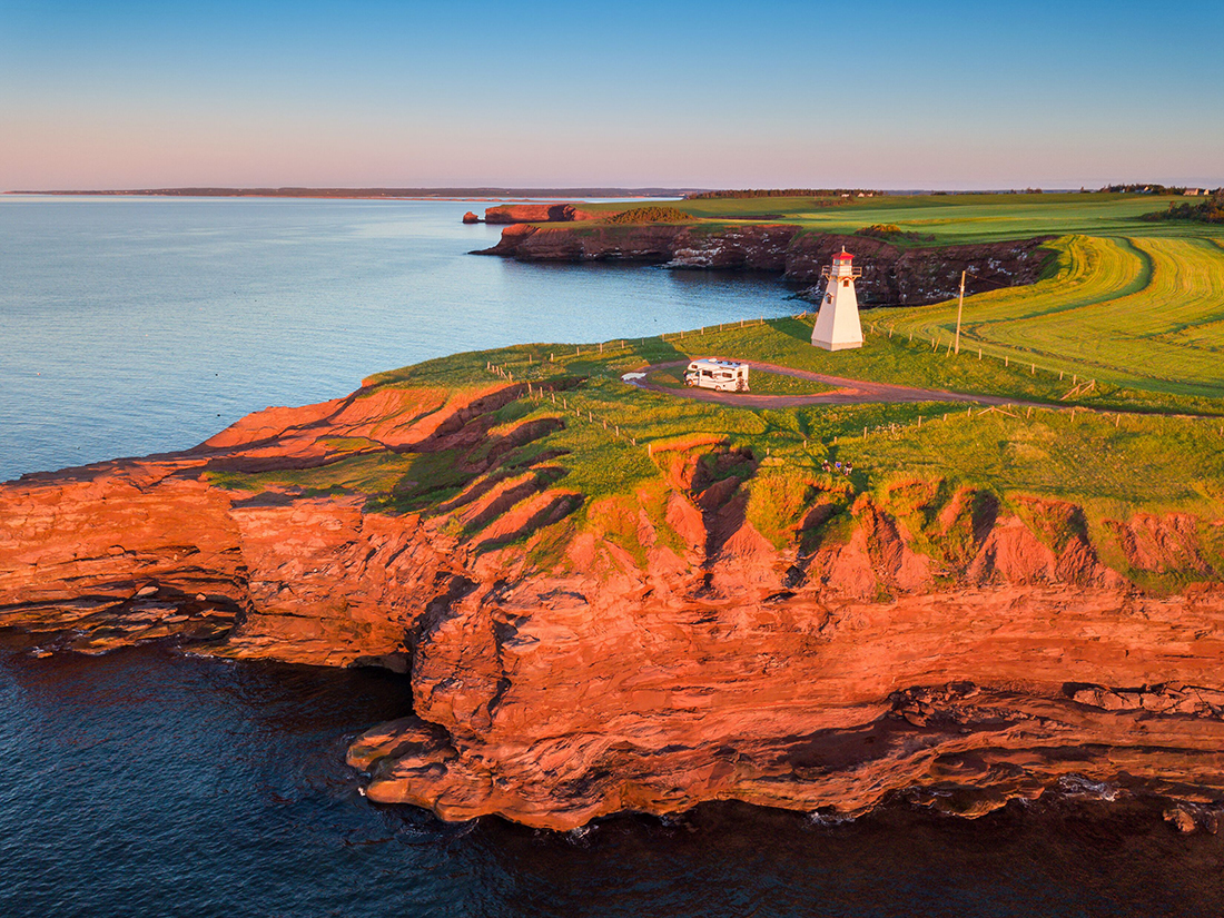 An RV drives near an elegant lighthouse on a bluff.