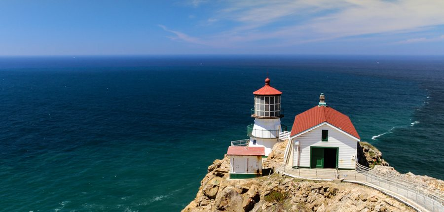 A lighthouse perched on the edge of a coast.