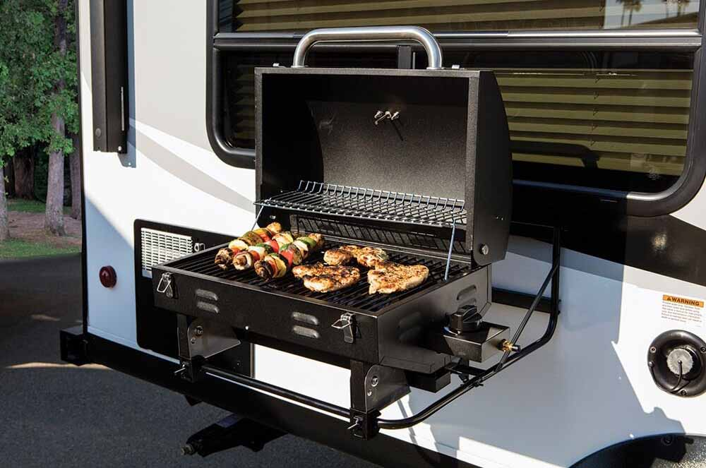 RV mounted barbecue cooking meat at Camping World of Denver