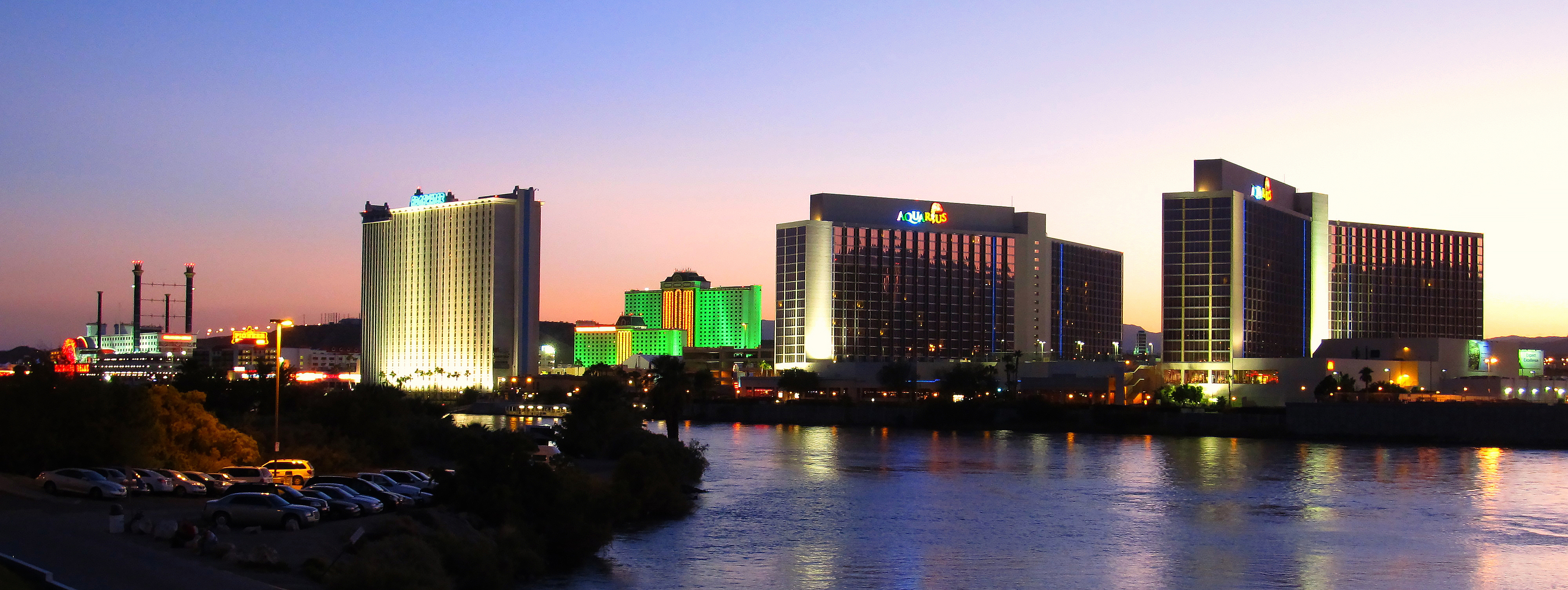 Gleaming and colorful casinos reflected on a river.