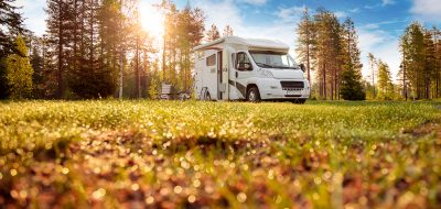 RV Parked in a spring meadow bathed in sunlight.