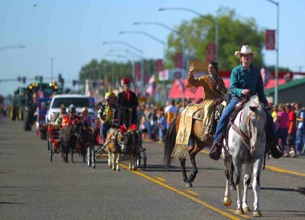 A small-town parade with riders and vehicles.