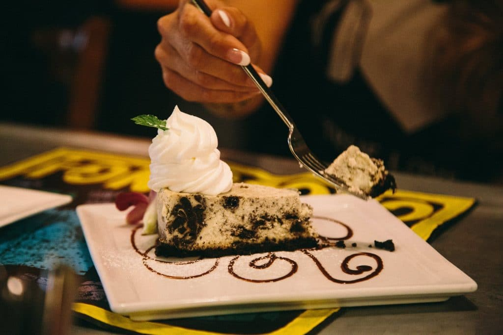 A diner digs into cheesecake topped with whipped cream.