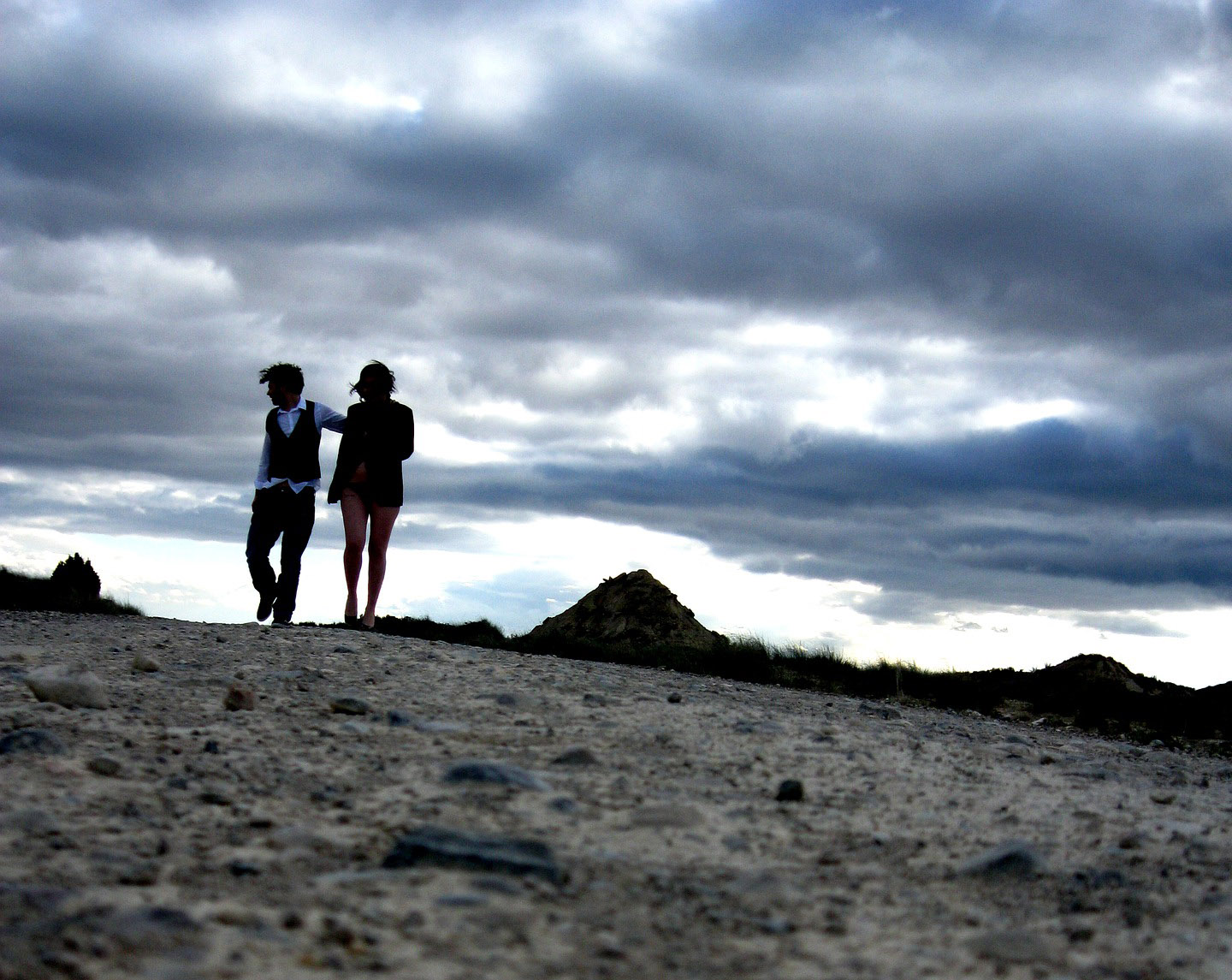 A couple walk across a barren desert landscape.