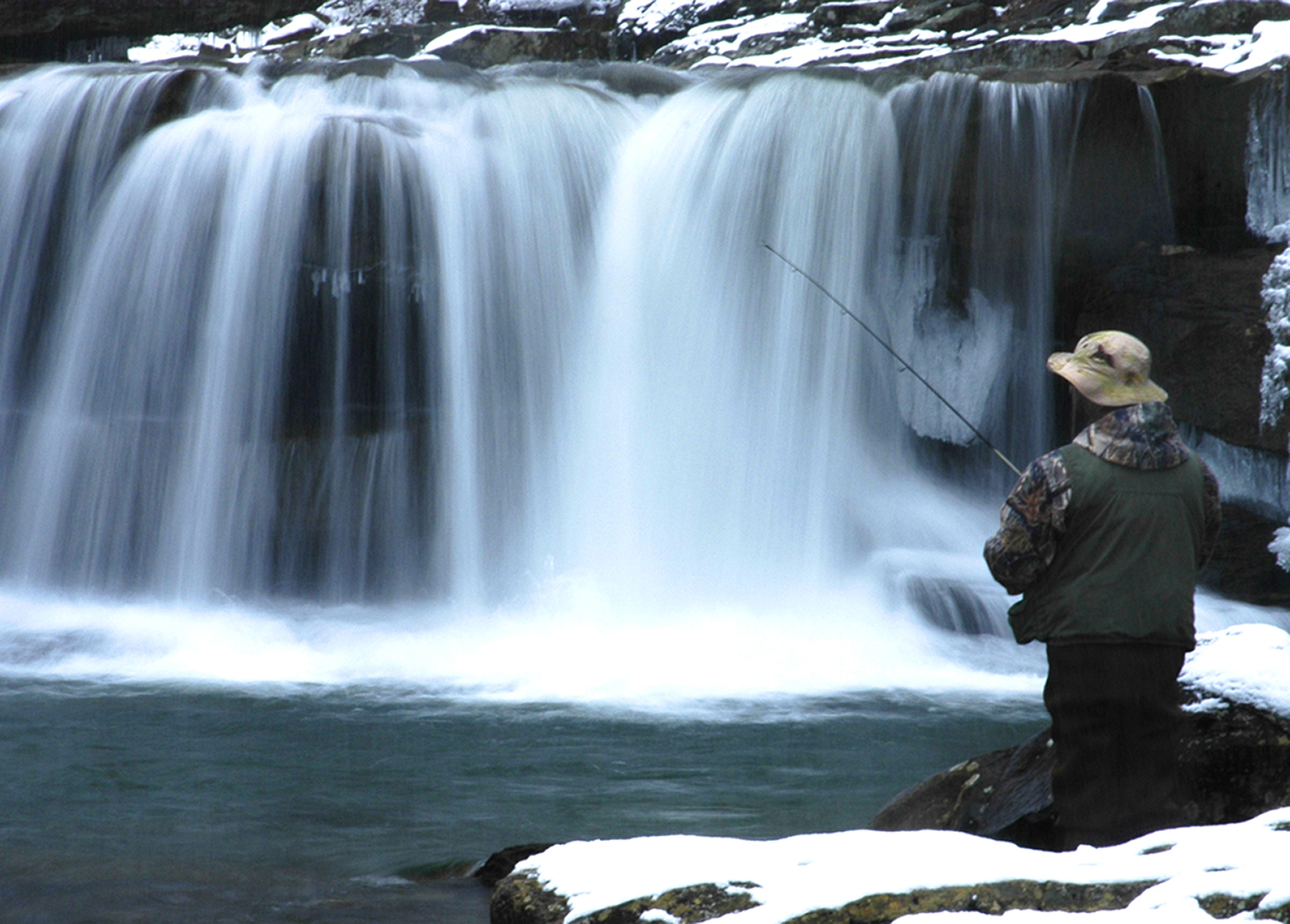 A man fishes at the foot of a waterfall.