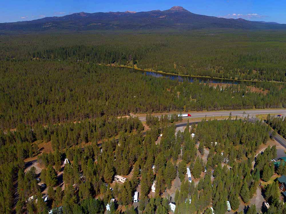 A highway cuts through a thick forest — aerial shot.