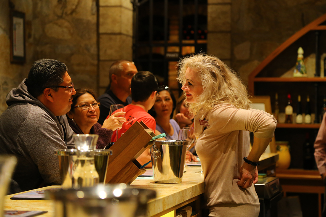 A wine server talks with customers in a Napa winery.