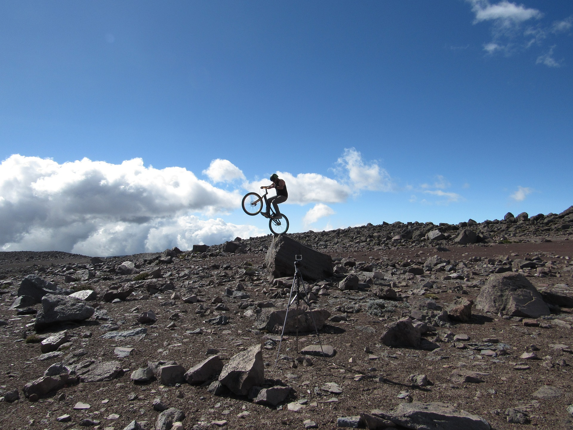 Riding a bicycle and doing tricks on a rocky landscape.