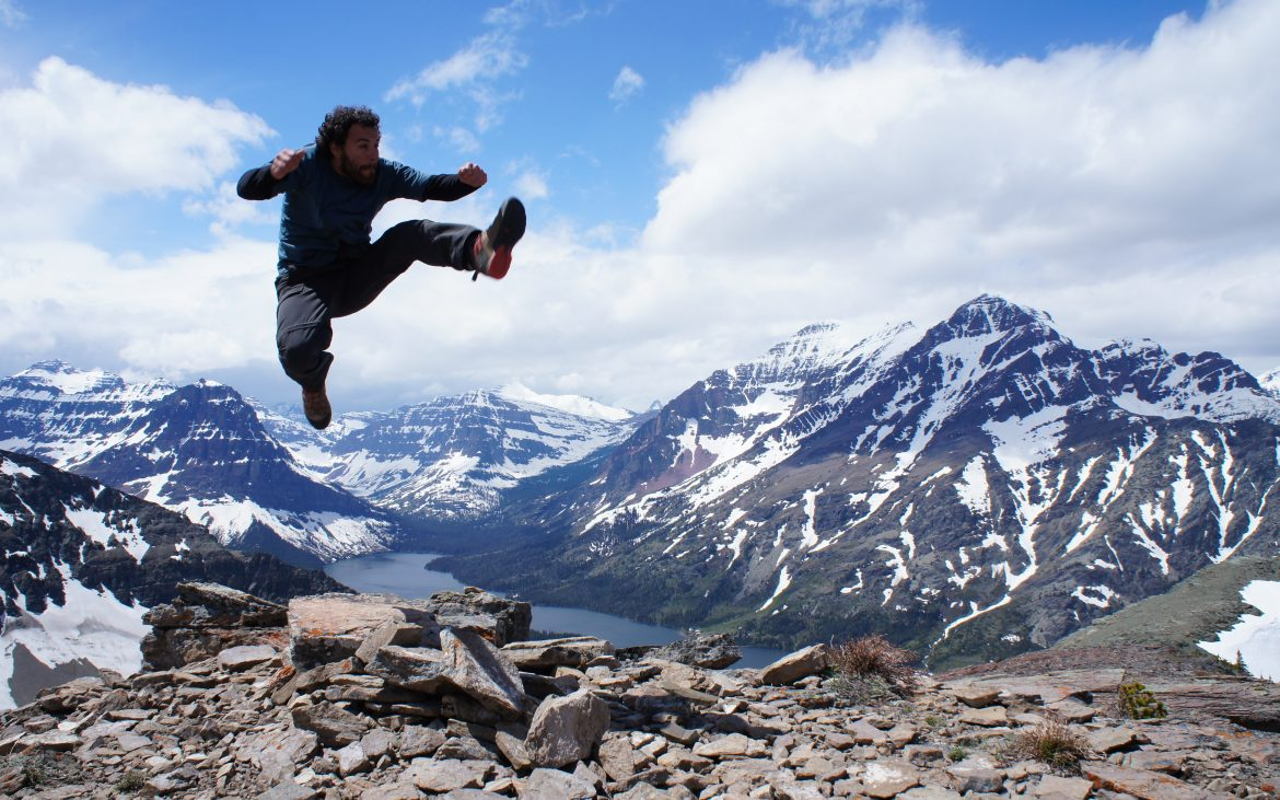 Bearded man jumping high at Glacier National Park