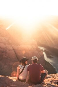 A couple sitting on a cliff overlooking a sunset.