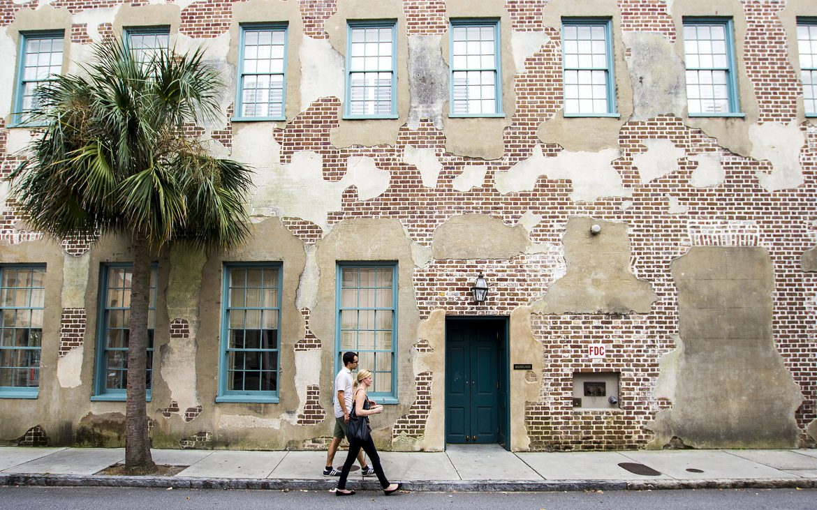 Man and woman walking next to old building in Charleston, South Carolina.