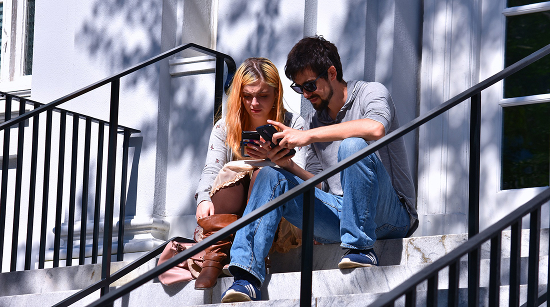 A couple look at their devices in Charleston.