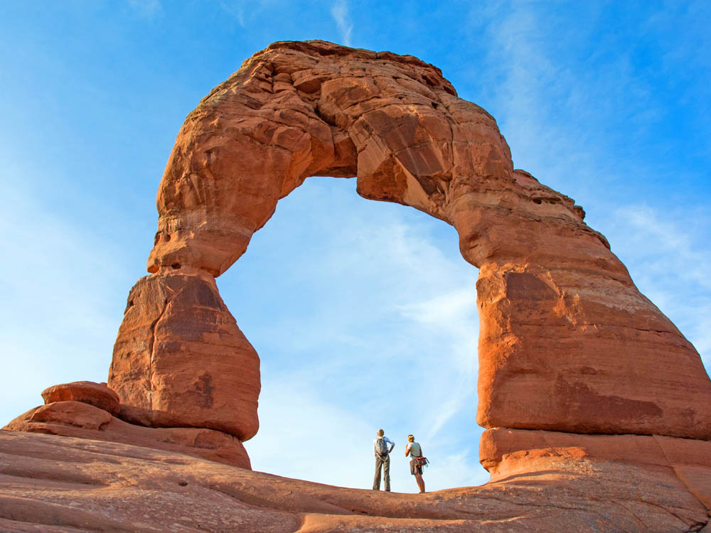 Two people gaze up at a rock arch.