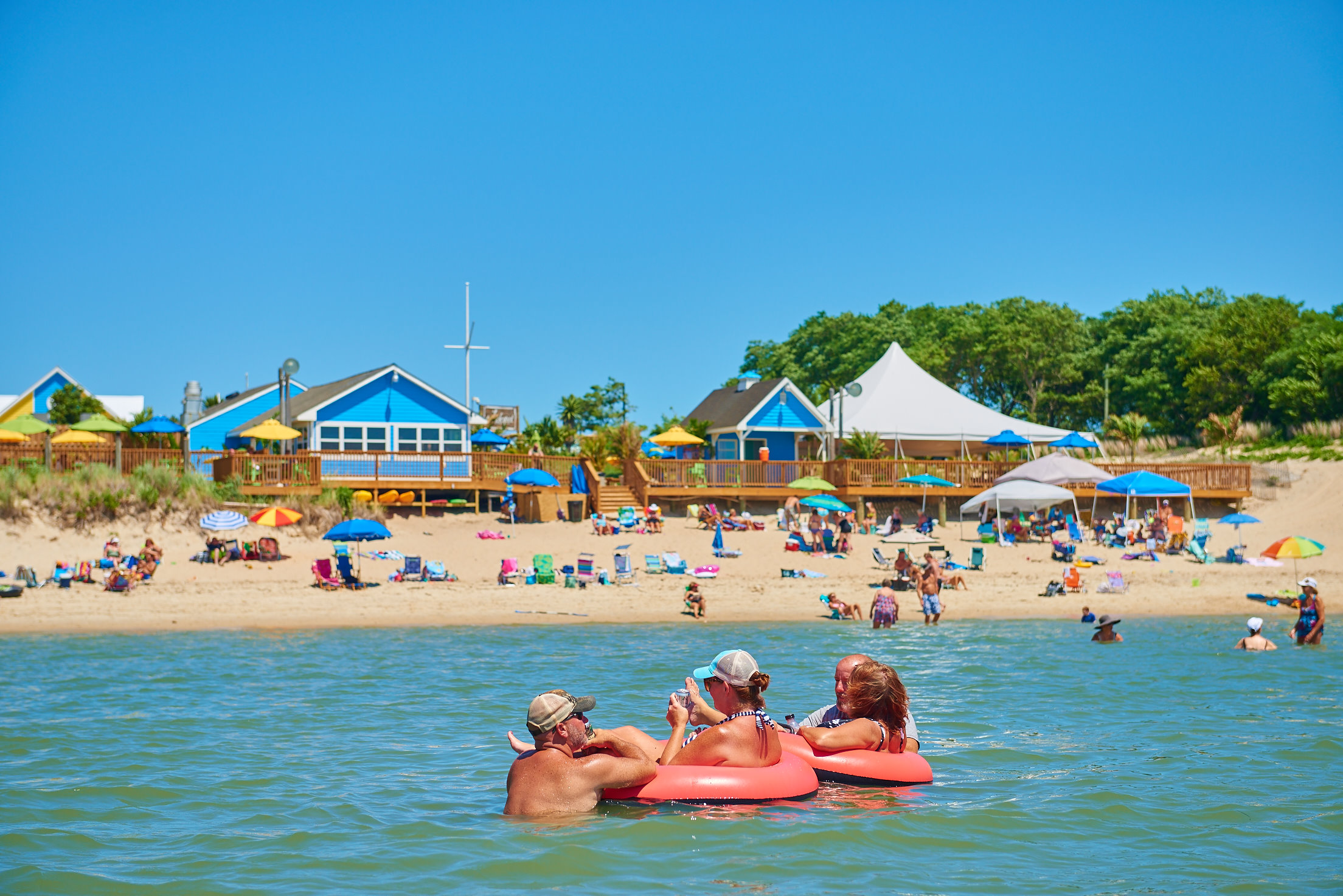 A group of people tubing on the water with a beach in the background.