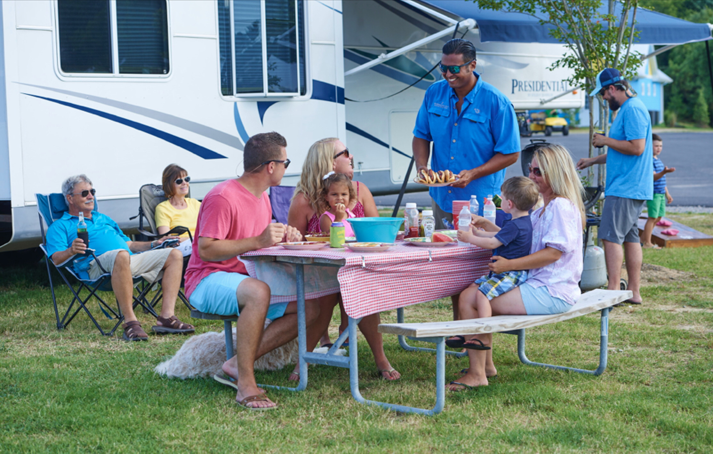 Families gather around a picnic table at RV park.