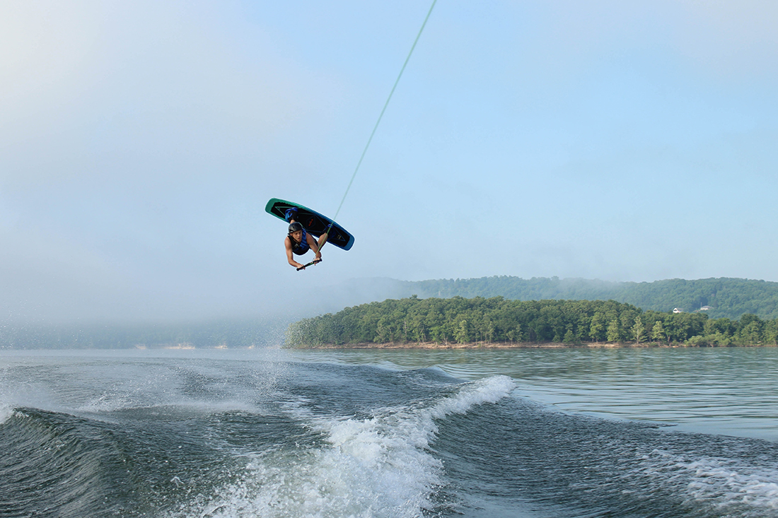 An extreme sports enthusiast kiteboards on a lake.