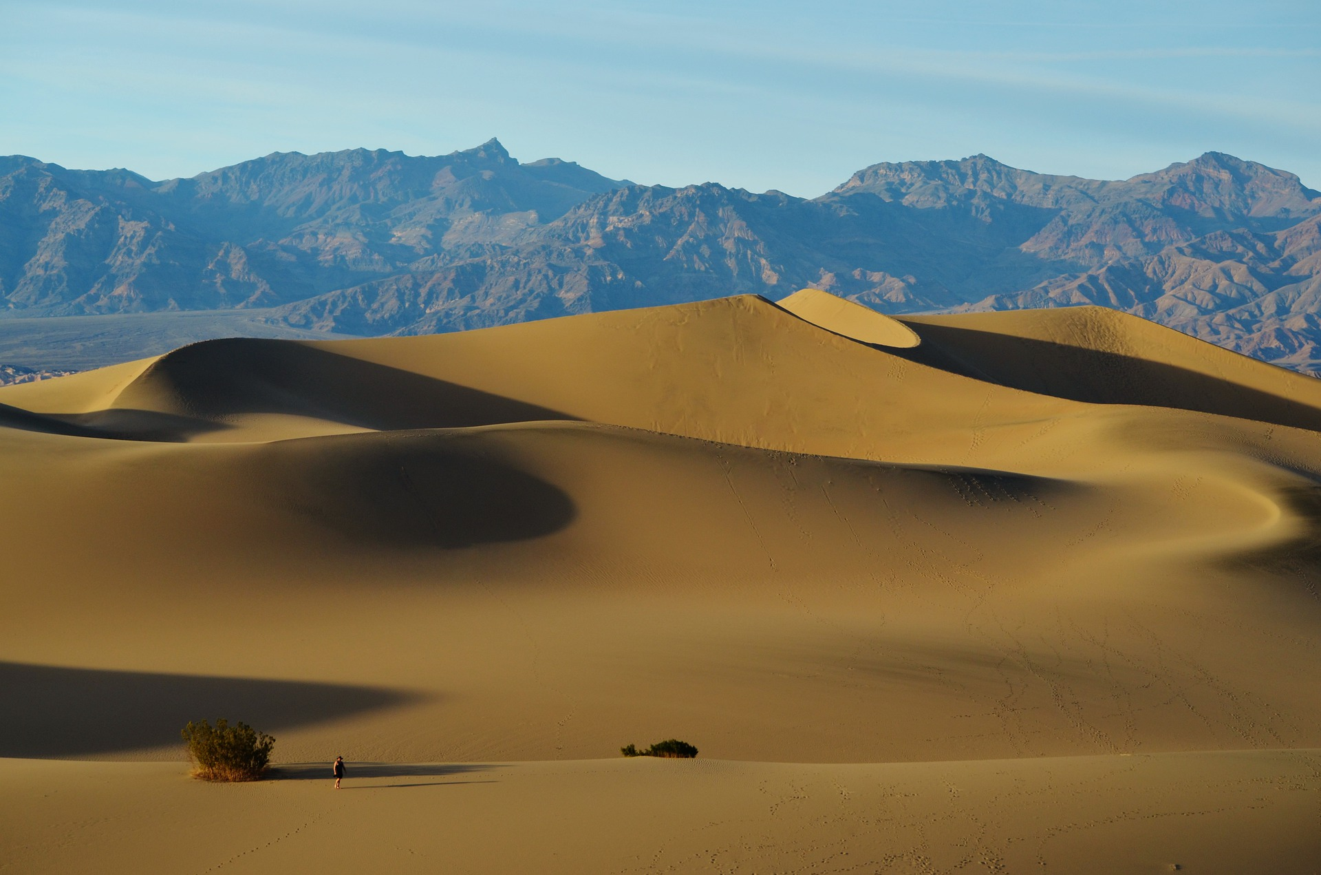 Creamy sand dunes in foreground, rugged mountains in background.
