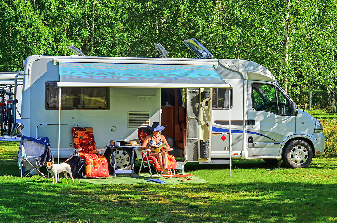 Woman lounging in RV with dog in patio area.