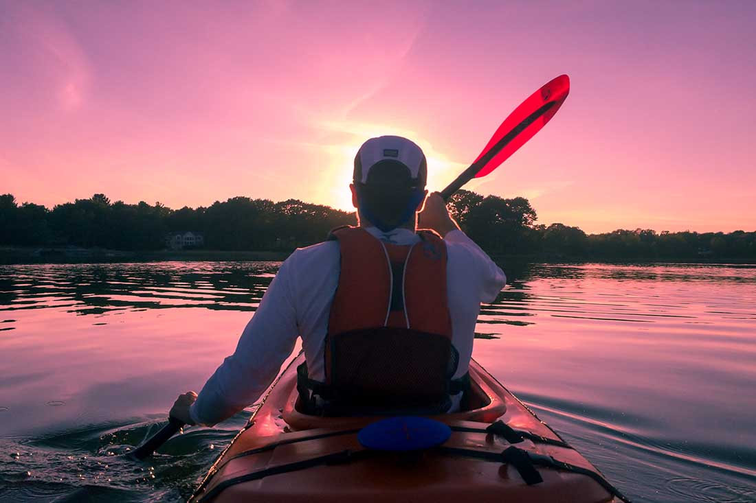 Kayaking on a lake toward sunset