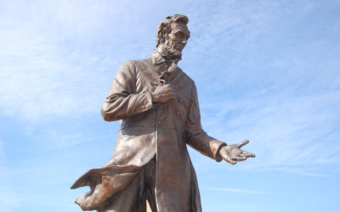 Abraham Lincoln Statue where Lincoln is gesturing either to pitch a product or give a speech.
