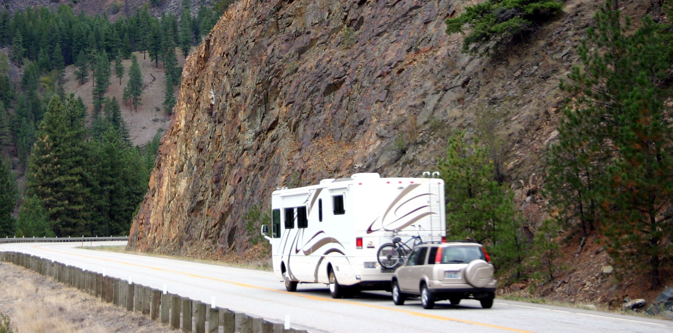 An RV driving along a road carved into a mountainside.