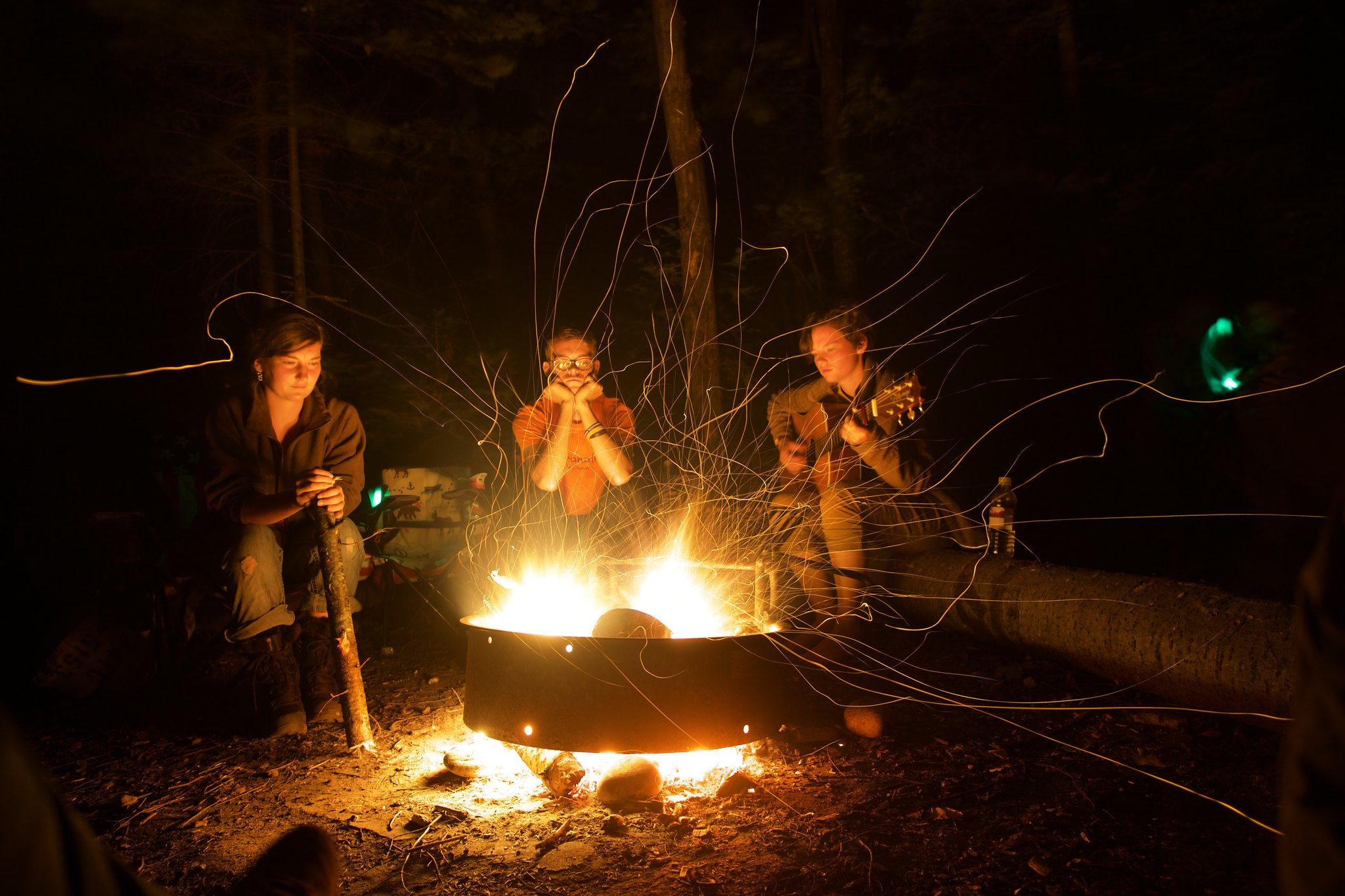 Three people gathered around a campfire.