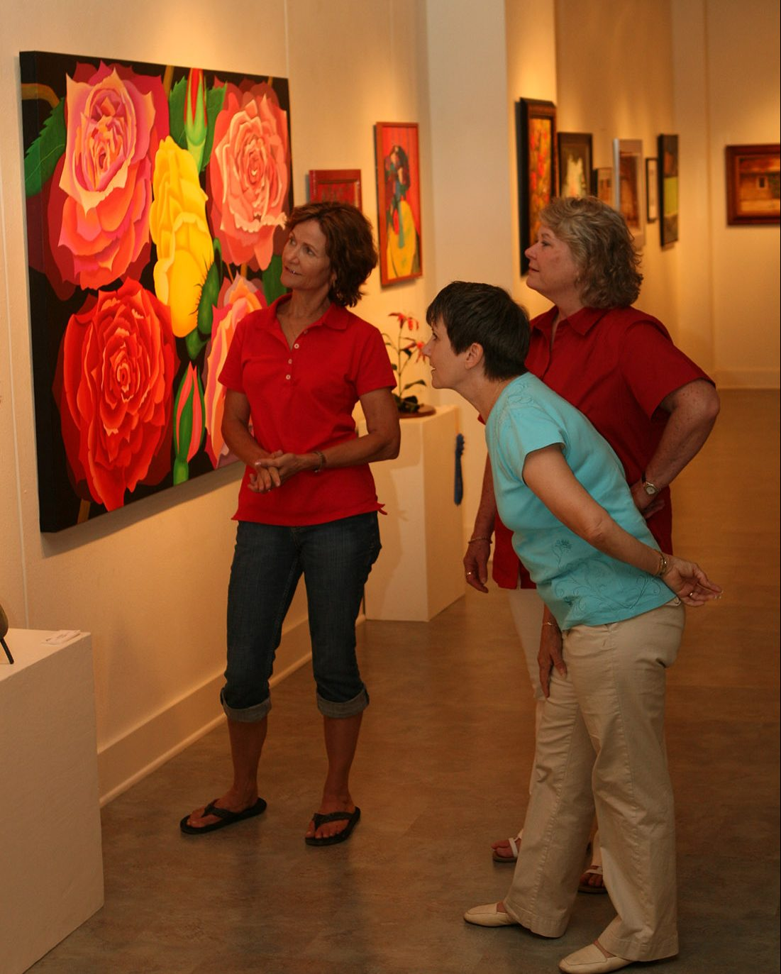 Women admire paintings on a wall.
