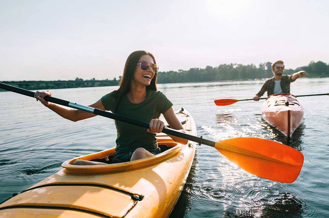 A man and woman enjoying kayaking together on lake.