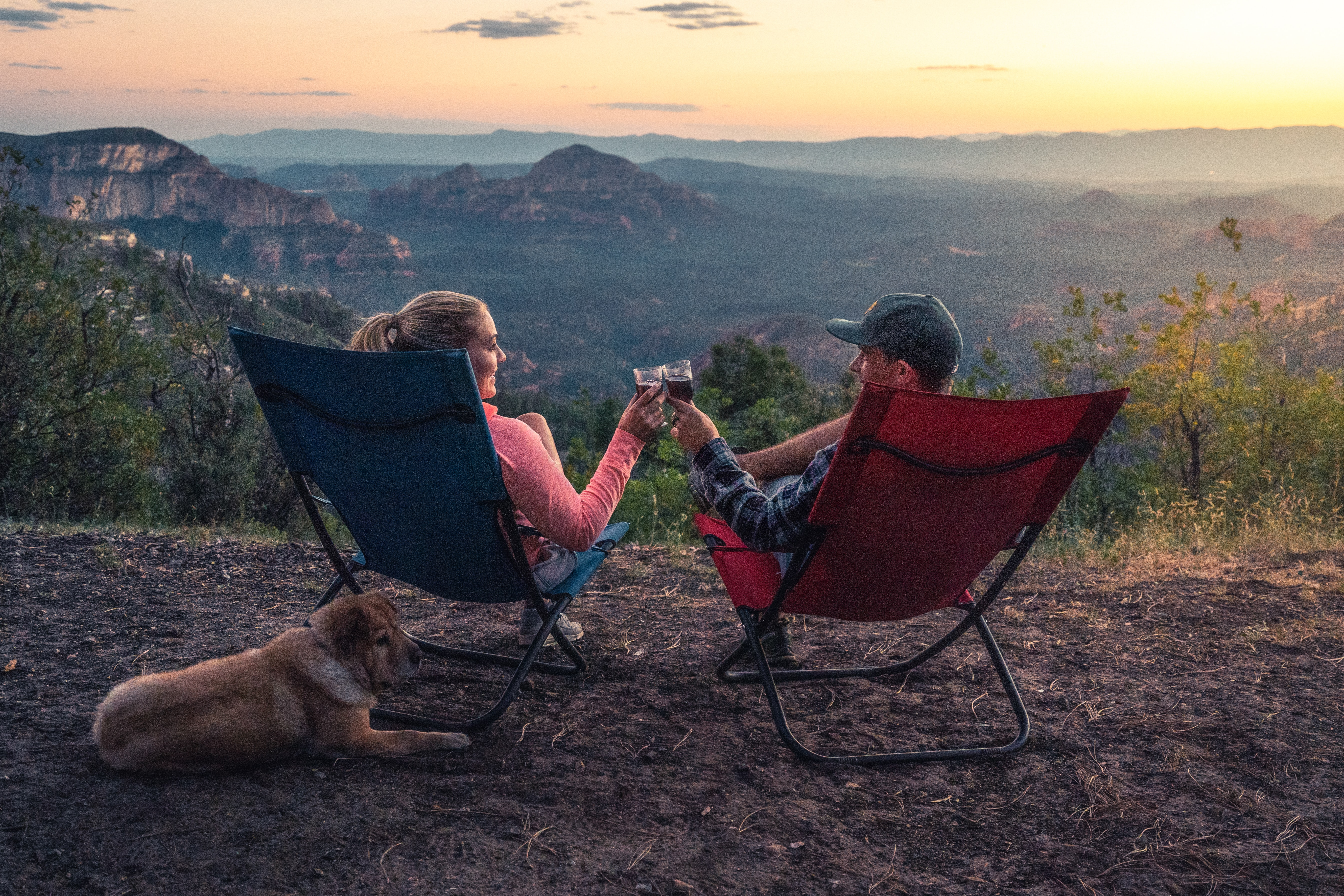 A couple makes a toast with wine as they enjoy a sweeping view.