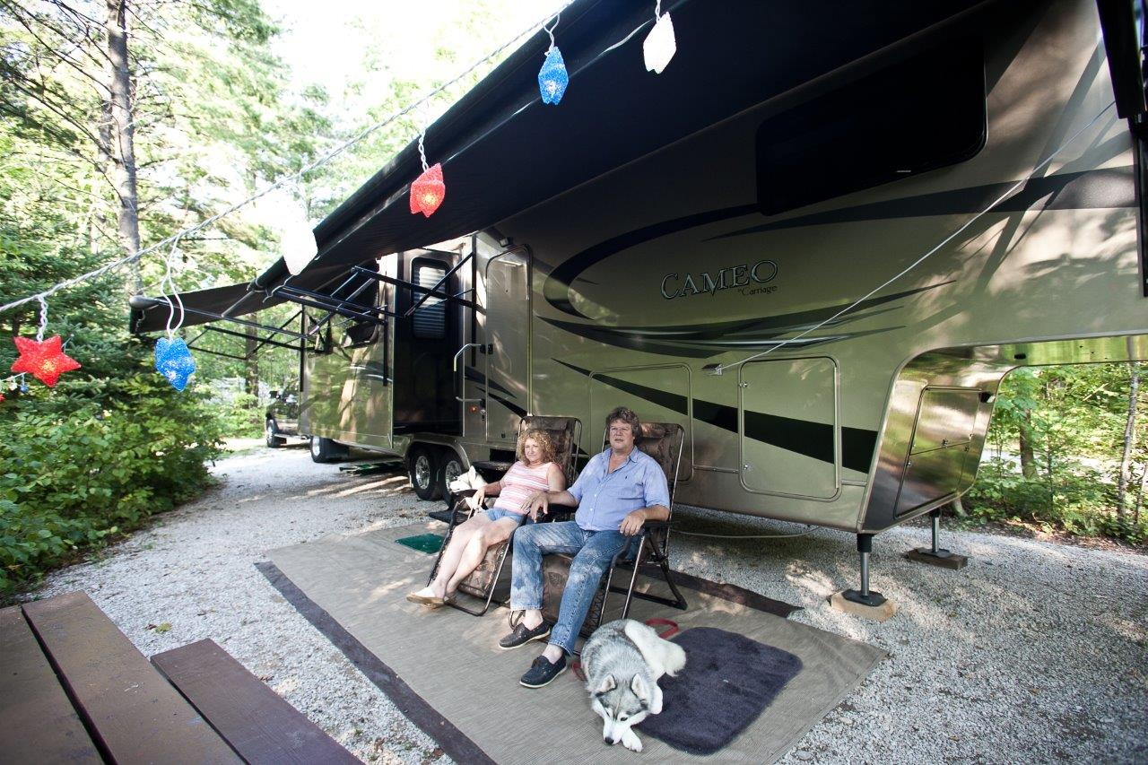 Guests relax outside of their RV.