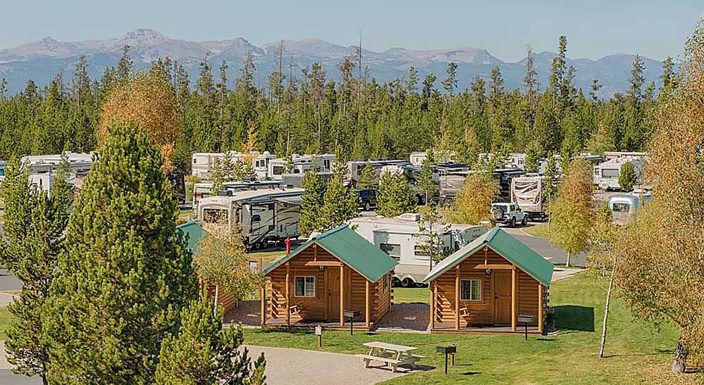 RVs and cabins in a forested setting.