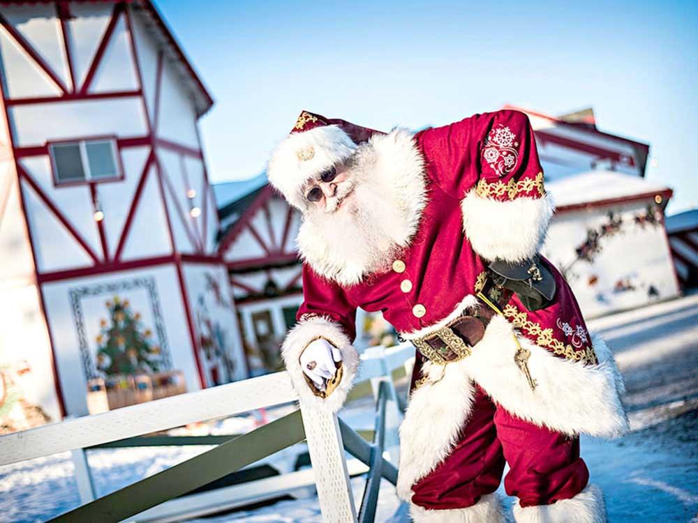 Santa standing near his house.