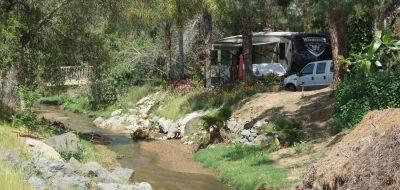 An RV campsite near a creek bed