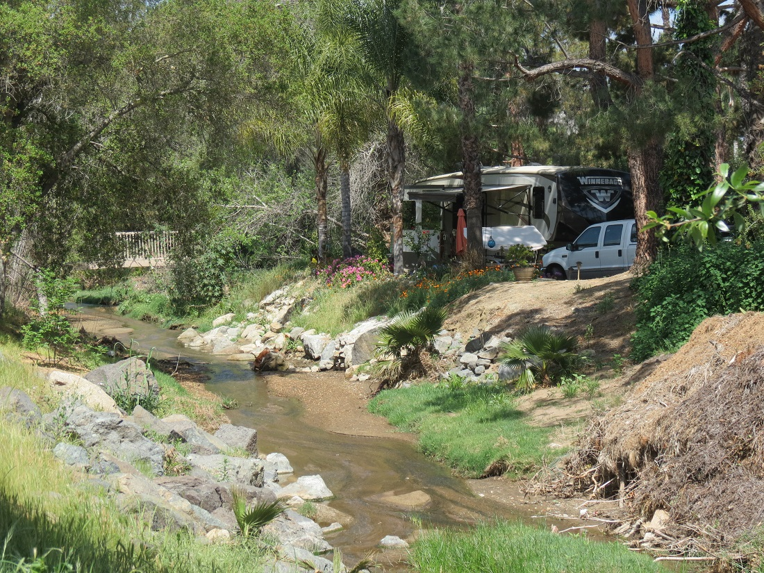 An RV campsite near a creek bed