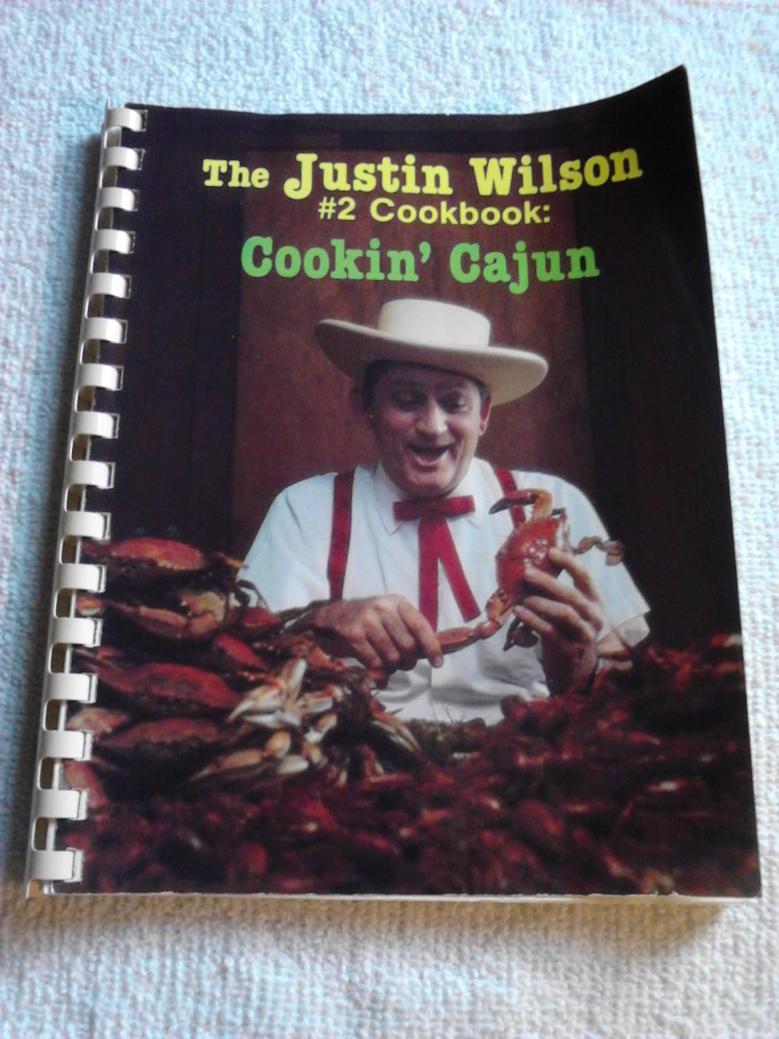 Cook book with cackling Cajun man with crustaceans.