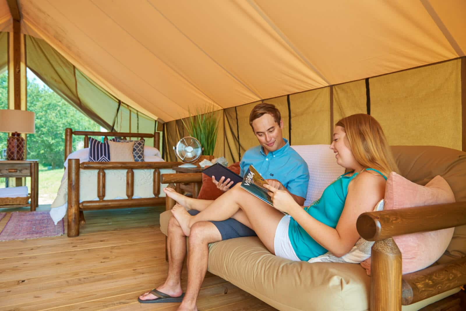 A couple lounges in a safari tent.