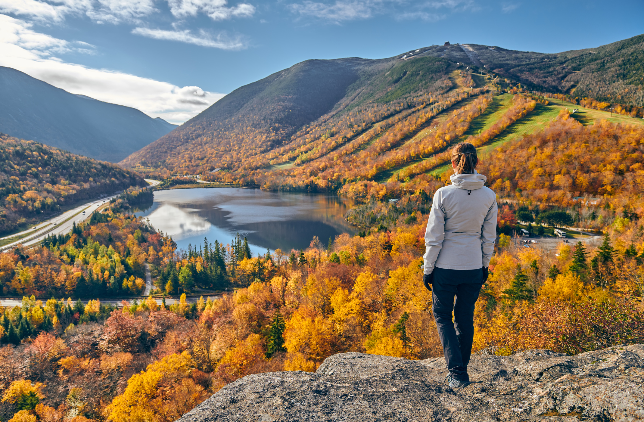 Woman hikes in fall landscape.