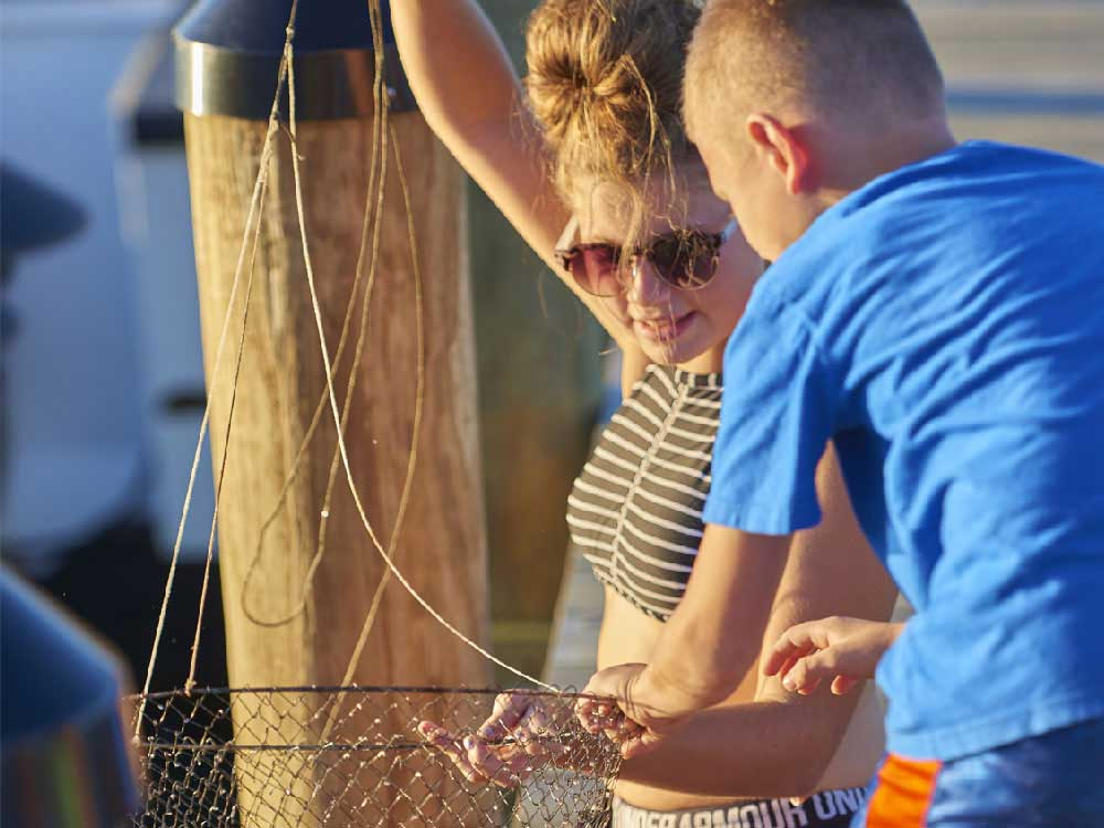 A teenager and child catch a crab in a net.
