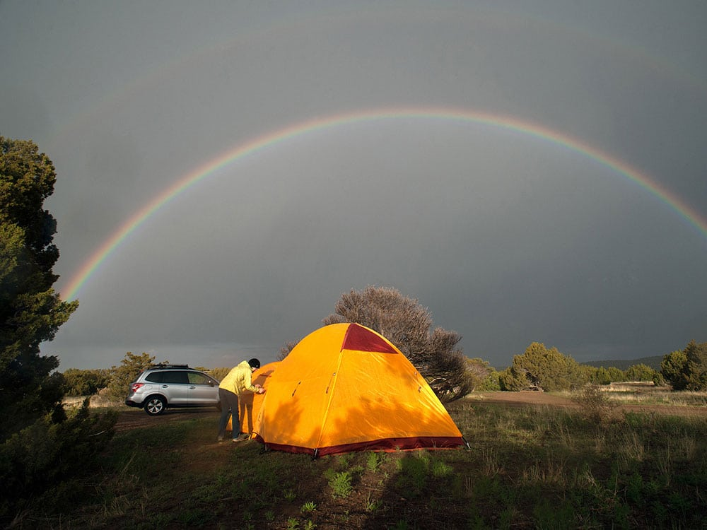 Guy camping in tent under a rainbow.