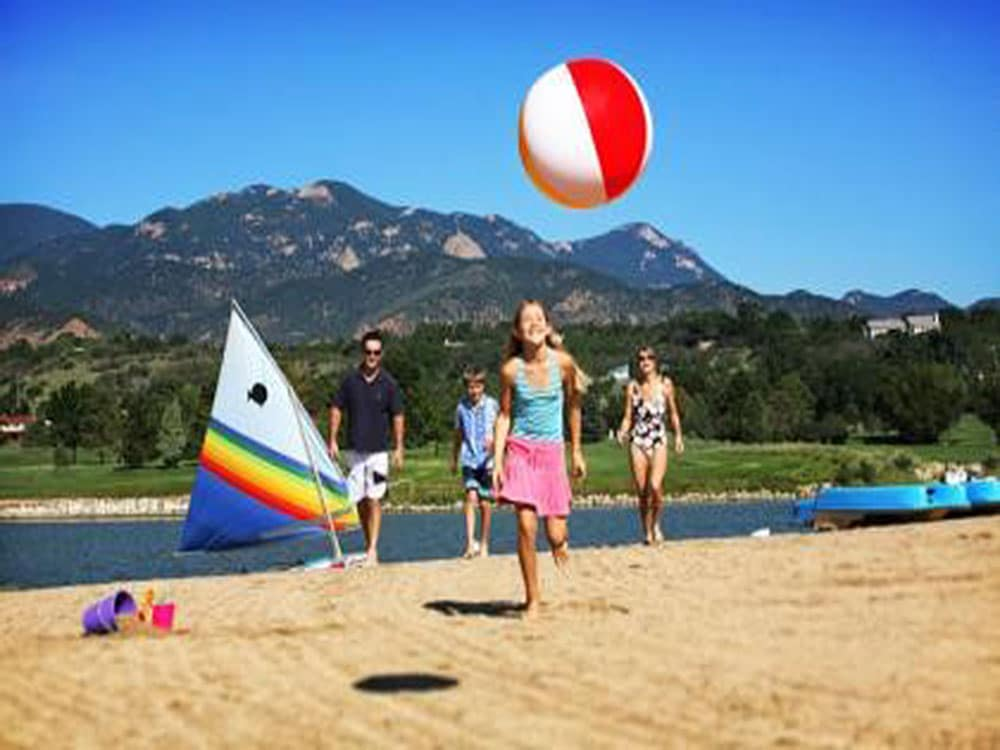 A family plays with a beach ball on a Colorado lake shore.