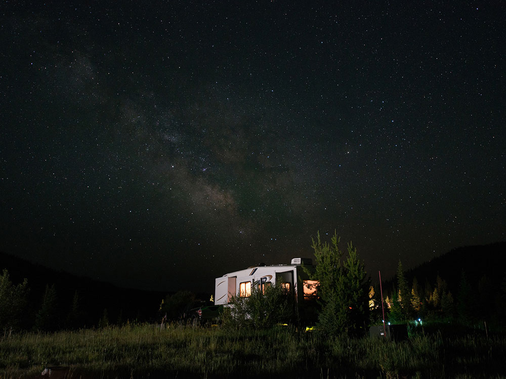 Fifth-wheel trailer parked under a starry sky.