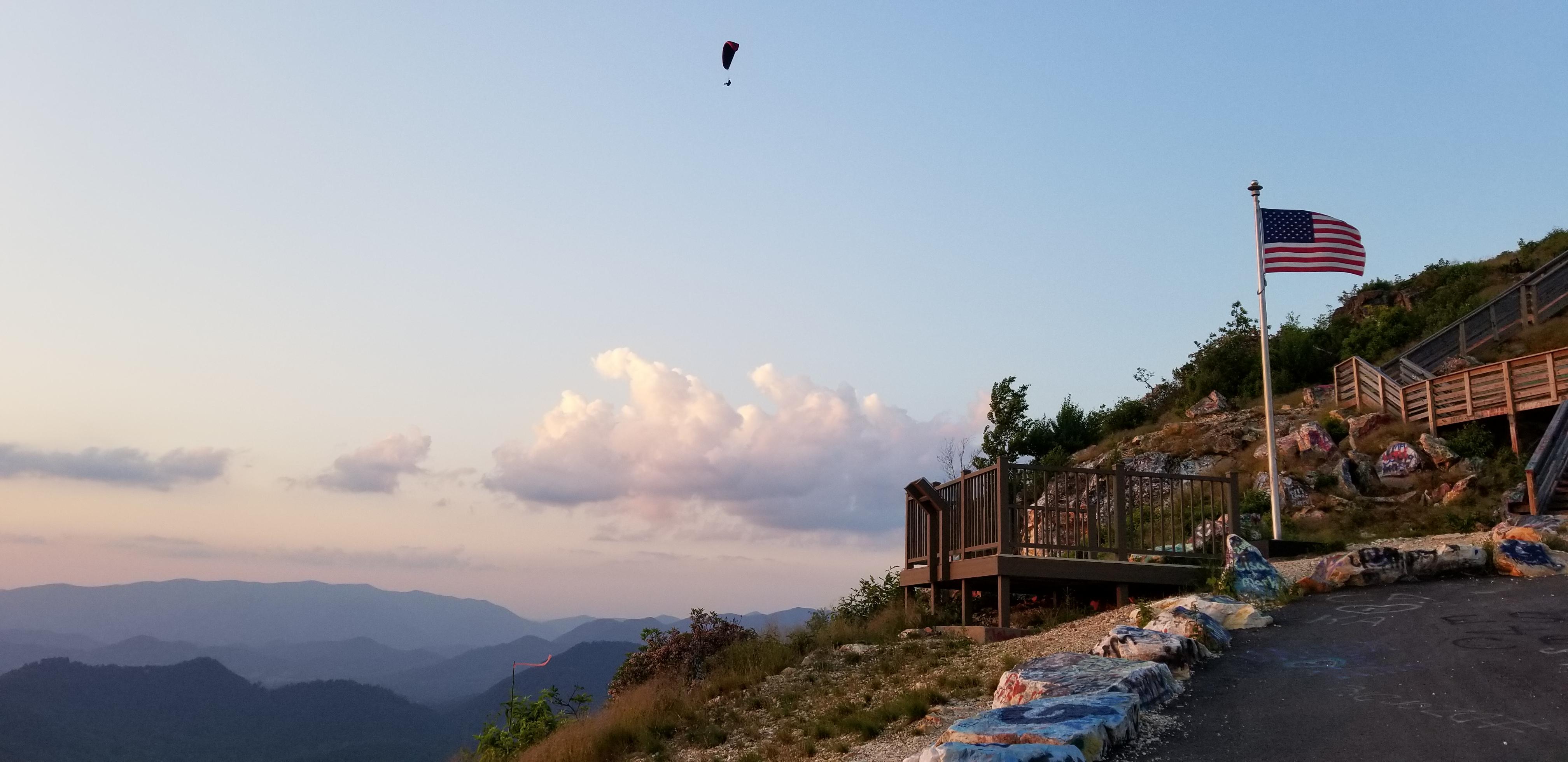 A paraglider sailing over a blue dusk sky.