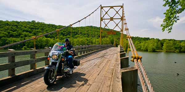A motorcyclist riding over a suspension bridge.