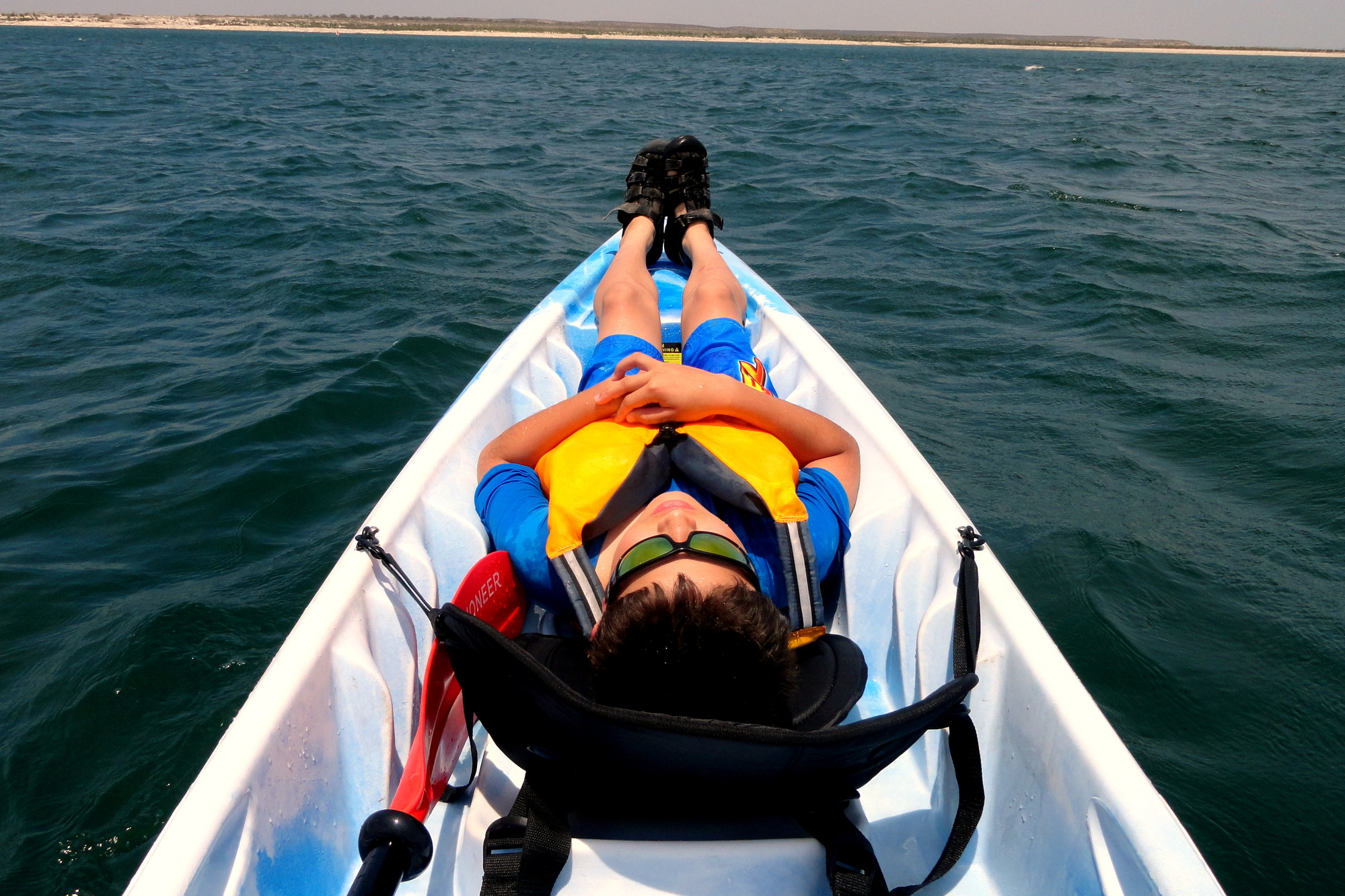 A paddler lies prone in his vessel